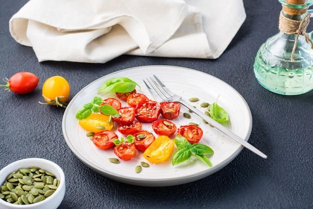 Suszone pomidory z bazylią, sezamem i dynią na talerzu na czarnym tle. jedzenie wegetariańskie