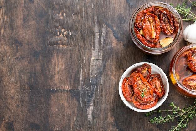 Suszone pomidory z oliwą z oliwek w słoiku na drewno