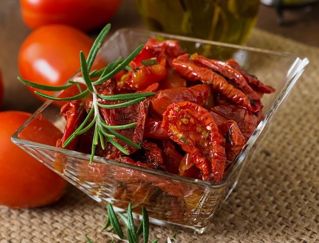 Suszone pomidory z ziołami i czosnkiem w drewnianej misce