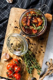 Suszone pomidory z ziołami i solą w oliwie z oliwek w szklance