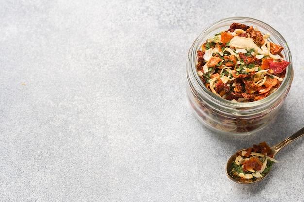 Suszone przyprawy, suszone pomidory, suszona marchewka, bazylia i zioła prowansalskie w szklanym słoju kopiowanie miejsca.