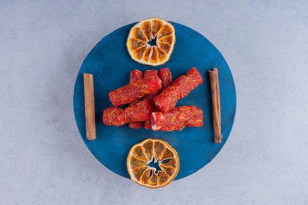 Suszone pulpy owocowe z orzechami i laskami cynamonu na niebieskiej tablicy.