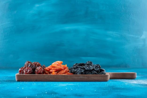 Suszone śliwki i morele na desce na niebieskiej powierzchni