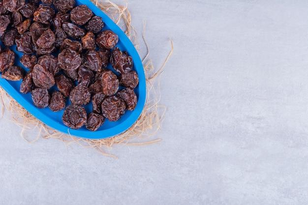 Suszone śliwki wiśniowe w naczyniu na betonowej powierzchni