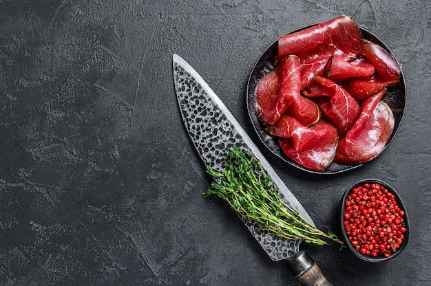 Suszone solone mięso wołowe bresaola pokrojone w cienkie plastry. czarne tło. widok z góry. skopiuj miejsce.