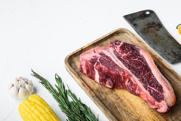 Suszone surowe mięso wołowe t-bone lub porterhouse stek z ziołami i zestawem soli, na białym tle kamienia, z kopią miejsca na tekst