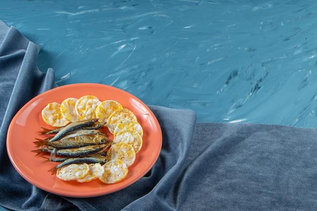 Suszone szproty i chipsy serowe w talerzu na ręczniku, na niebieskim tle.