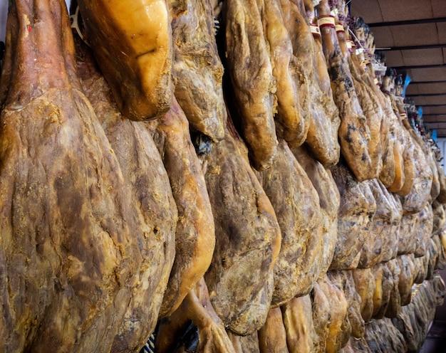 Suszone udka wieprzowe wiszą na targu mięsnym. hiszpańskie danie narodowe szynki lub szynki w sklepie spożywczym. iberyjska wieprzowina zakupy w supermarkecie hiszpania. suszona i peklowana szynka wisząca. rynek sprzedaje surowe produkty mięsne