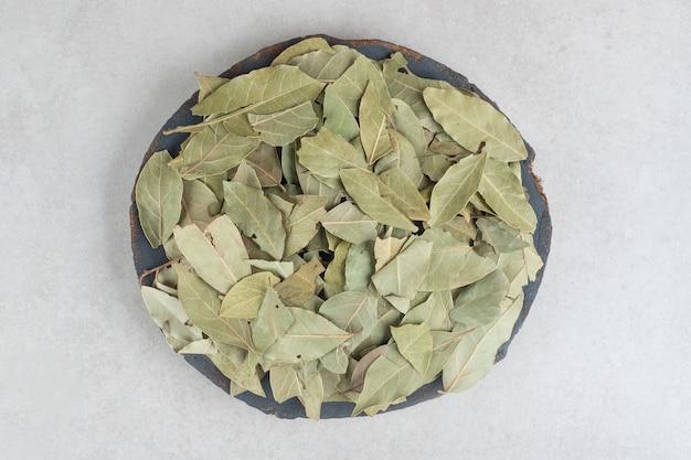 Suszone zielone liście laurowe na drewnianym talerzu.