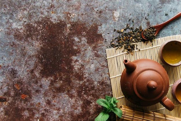 Suszone zioła; mennica; czajnik i herbata ziołowa na podkładce na rustykalnym tle