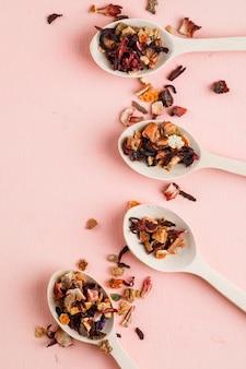 Suszone zioła w drewnianych łyżkach na różowo.