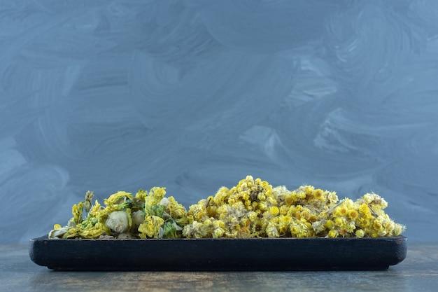 Suszone żółte kwiaty na ciemnym talerzu.