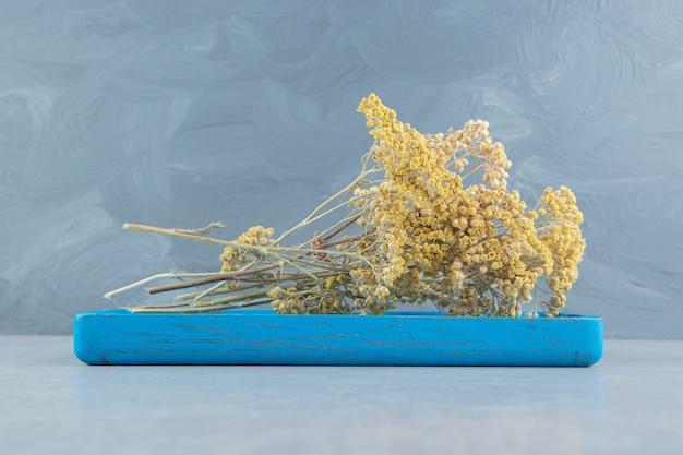 Suszone żółte kwiaty na niebieskim pokładzie.
