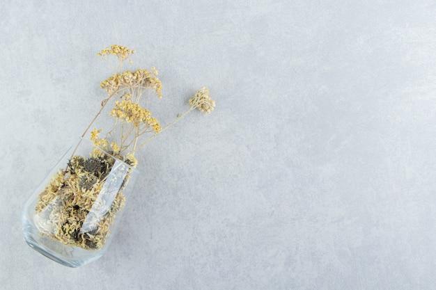 Suszone żółte kwiaty ze szklanego kubka