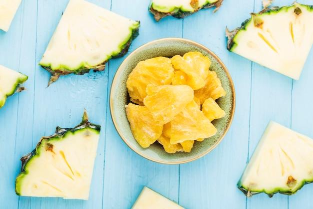 Suszony ananas w misce na ścianie z drewna