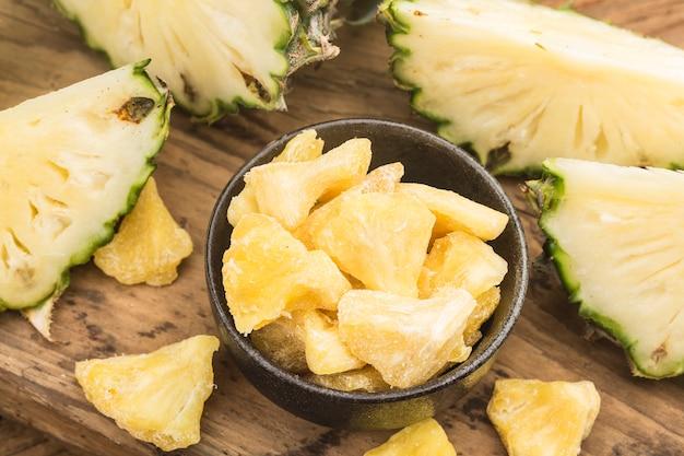 Suszony ananas w misce na tle drewna