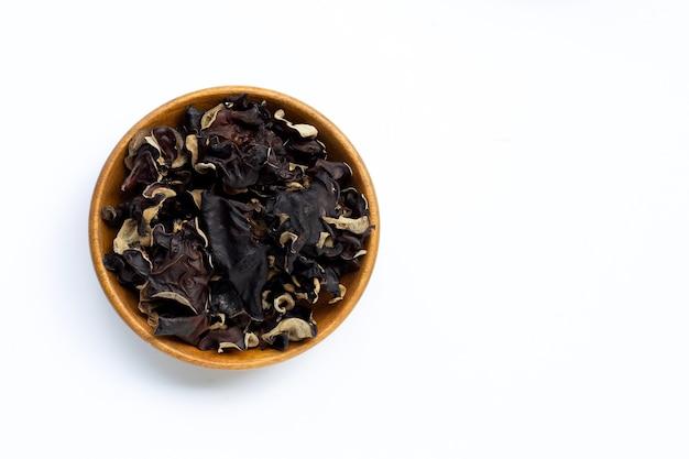 Suszony czarny grzyb w drewnianej misce.