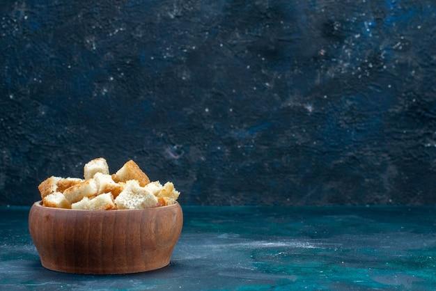 Suszony krojony chleb wewnątrz brązowej miski na ciemnoniebieskim tle