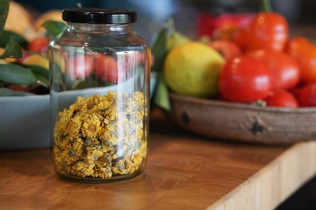 Suszony kwiat chryzantemy w szklanym słoju w kuchni. ziołowa herbata ziołowa