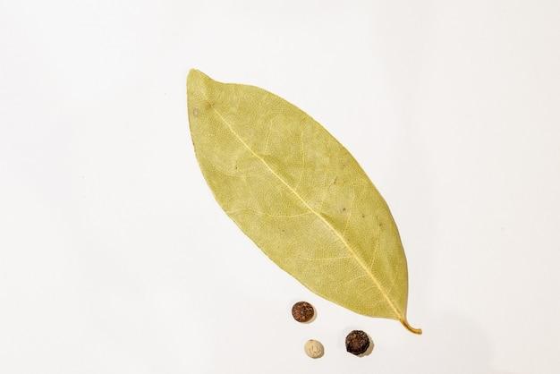 Suszony liść laurowy i ziarna pieprzu na białym tle.