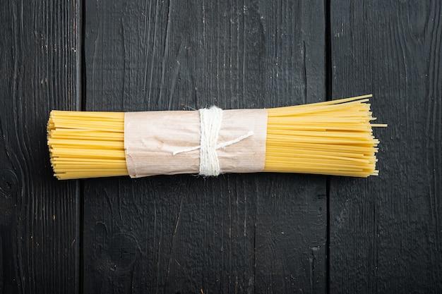 Suszony makaron spaghetti, na czarnym drewnianym stole