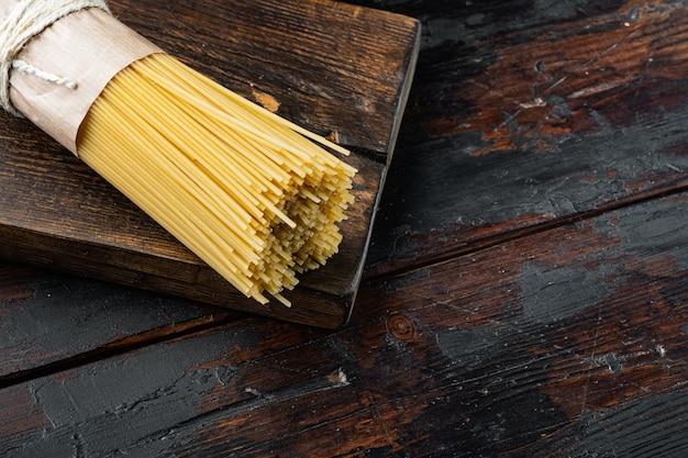 Suszony makaron spaghetti, na drewnianej desce do krojenia, na starym ciemnym drewnianym stole