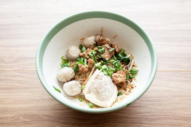 Suszony makaron z wieprzowiną tofu, klopsikiem i gotowaną wieprzowiną w dużej misce na tle drewna