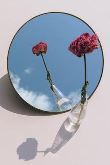 Suszony różowy kwiat piwonii w przezroczystym wazonie odbity w lustrze
