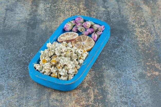 Suszony rumianek i pączkujące róże na niebieskim talerzu.
