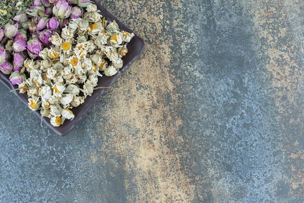 Suszony rumianek, róża i liście na ciemnym talerzu.