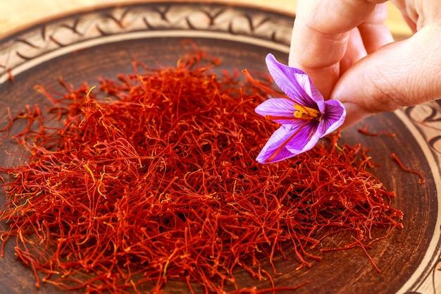 Suszony szafran z kwiatkiem we wzorzystym talerzu ceramicznym. przyprawa szafranowa stosowana w żywności i tradycyjnej medycynie