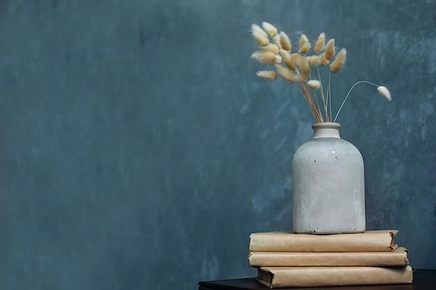 Suszy kwiaty w antycznej wazie na lazurowym niebieskim tle. miejsce na tekst.