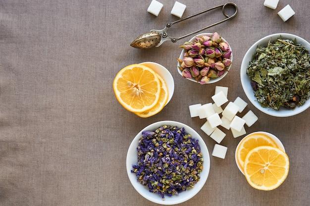 Suszy ziołowej i kwiat herbaty w pucharach na brown tle