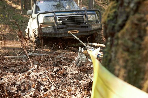 Suv 4x4 wyciąga się z pułapki za pomocą wyciągarki zaczepionej o drzewo. ekstremalne wyścigi terenowe