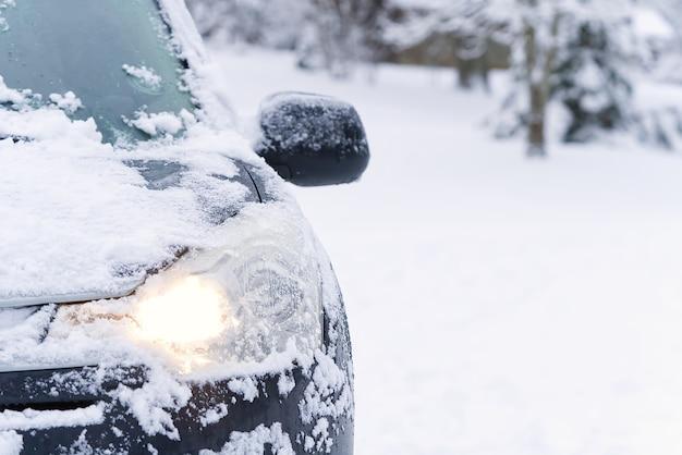 Suv samochód jest pokryty śniegiem w zimowy poranek na wsi. koncepcja jazdy w okresie zimowym ze śniegiem na drogach.