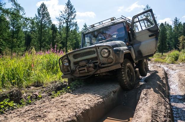 Suv utknął w koleinie na złej nieprzejezdnej drodze w lasach syberii. rosja