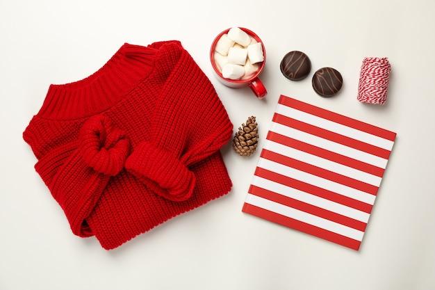 Sweter, filiżanka kawy z ptasie mleczko, stożek, zeszyt, ciastka i ciąg na białym tle