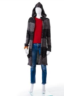 Sweter w paski z kapturem. kobiecy manekin w płaszczu sweterkowym. miękka odzież wierzchnia damska na wystawie. ubrania na suchą chłodną pogodę.