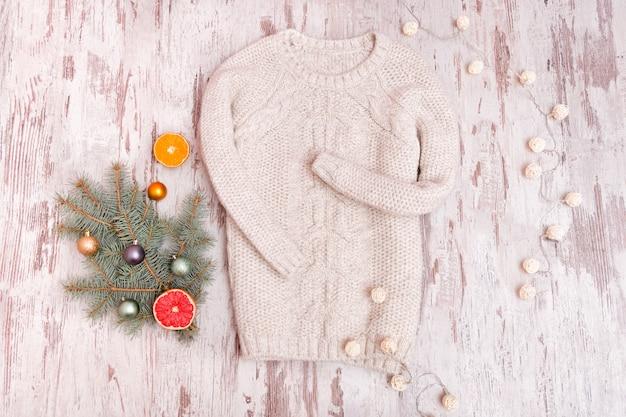 Sweter z dzianiny, ozdobiona gałąź jodły i girlanda