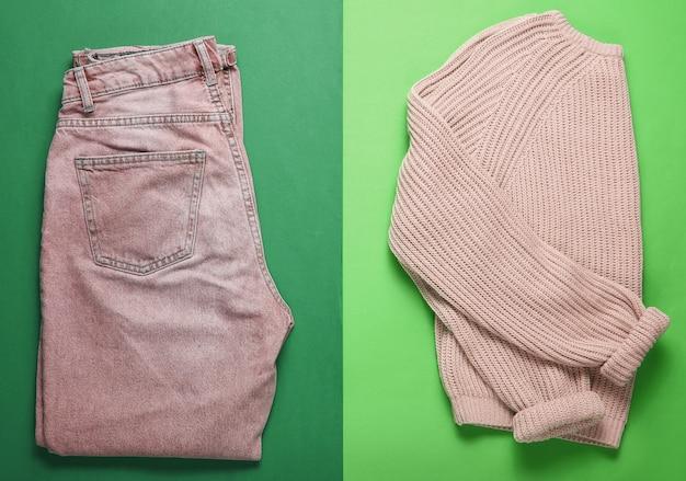 Sweter z dzianiny typu flat lay, modne niebieskie dżinsy na zielonym tle