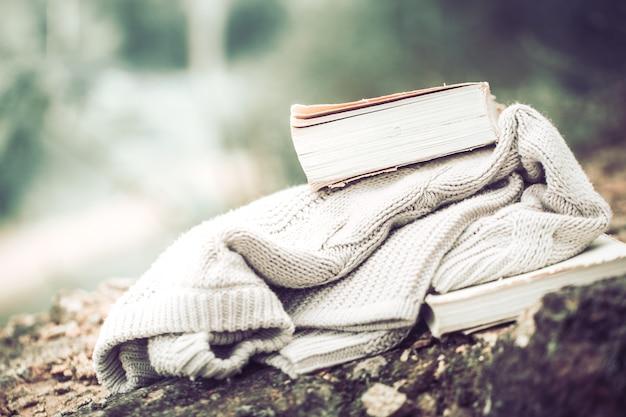 Sweter z dzianiny z książką na tle przyrody
