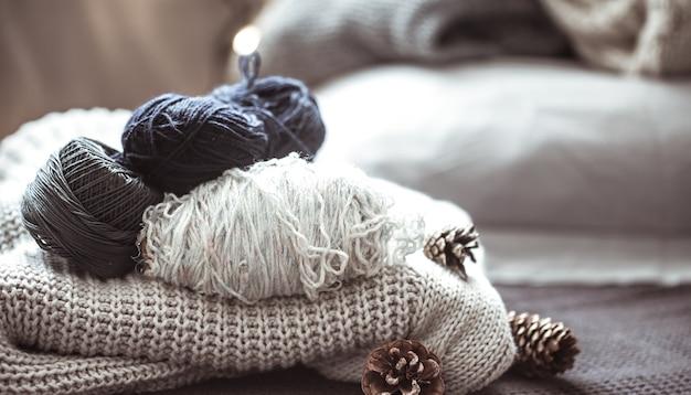 Sweter z dzianiny z kulkami przędzy, pojęcie ciepła i komfortu, hobby, tło, zbliżenie