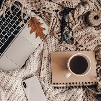 Swetry i filiżanka herbaty z notatnikiem, laptopem i telefonem