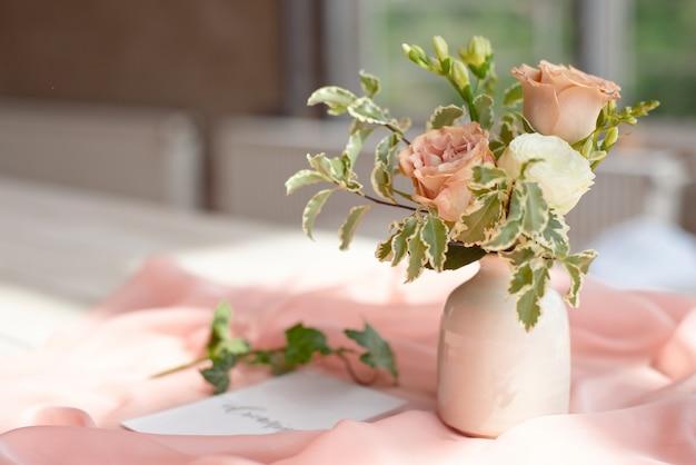 Świadectwo urodzinowe z zaproszeniem na ślub dla spa lub opiekuńczej karty z listem na białym drewnianym stole przed oknem panoramicznym