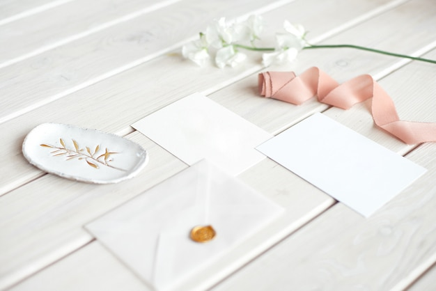 Świadectwo urodzinowe zaproszenia ślubne na spa lub opiekę zdobione karty list na białym drewnianym stole z gałęzi białych kwiatów.