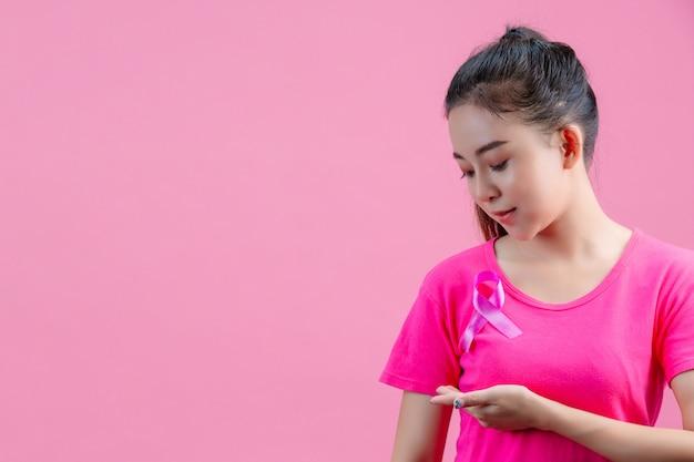 Świadomość raka piersi, kobieta w różowej koszulce z satynową różową wstążką na piersi, wspierająca świadomość raka piersi