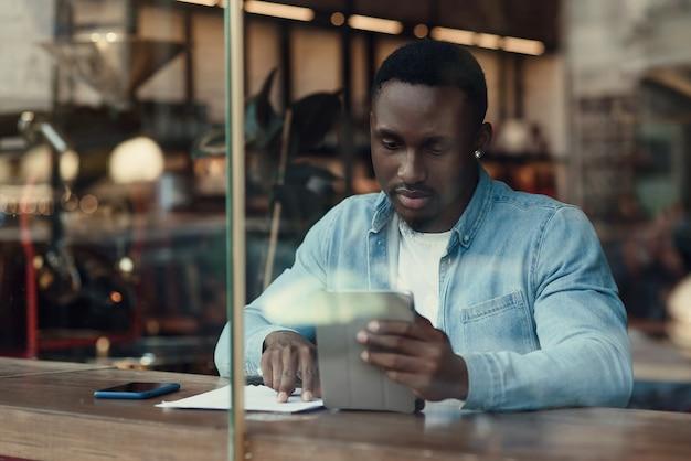 Świadomy czarny przedsiębiorca używa komputera typu tablet, siedząc w kawiarni z kawą przy oknie.