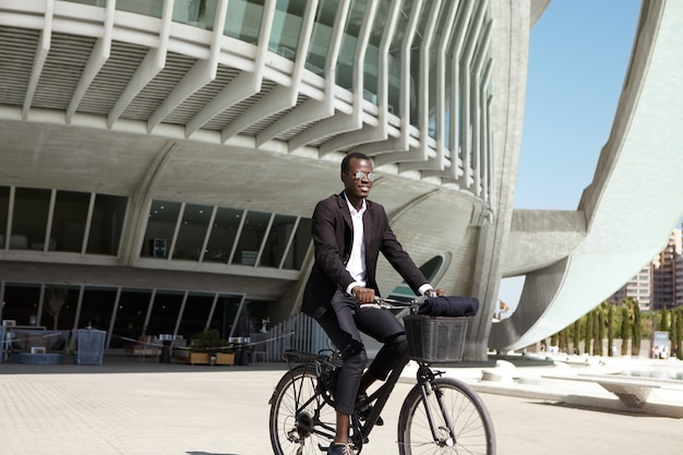 Świadomy ekologicznie młody czarny biznesmen europejski w czarnym garniturze i okularach przeciwsłonecznych na rowerze do kawiarni na rowerze retro podczas przerwy obiadowej w słoneczny dzień