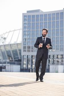 Świat miejski. pełna długość uśmiechniętego biznesmena, który pije kawę idąc do pracy w mieście