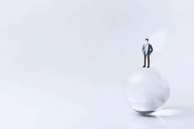 Świat szkła z zabawkowym modelem biznesmena. świat koncepcji biznesowej